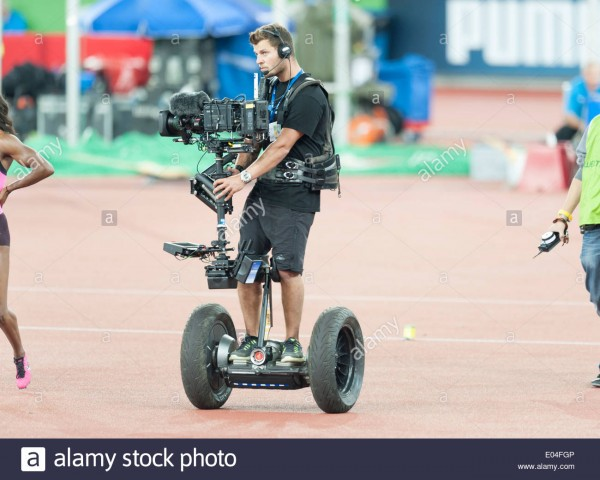 camera-operator-standing-on-a-segway-and-equipped-with-steadicam-camera-E04FGP.jpg